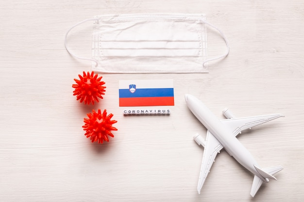 Model samolotu i maska na twarz oraz flaga słowenii. koronawirus pandemia. zakaz lotów i zamknięte granice dla turystów i podróżników z koronawirusem covid-19 z europy i azji.