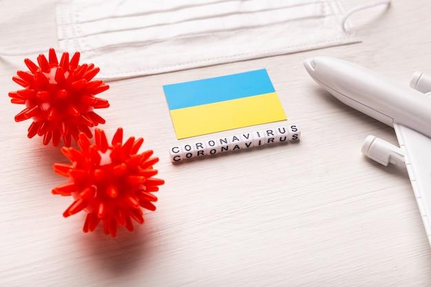 Model samolotu i maska na twarz oraz flaga ukrainy. koronawirus pandemia. zakaz lotów i zamknięte granice dla turystów i podróżników z koronawirusem covid-19 z europy i azji.