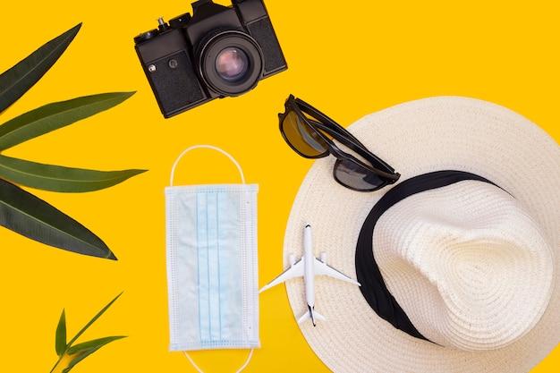 Model samolotu, laptop, telefon, maska medyczna, aparat fotograficzny i okulary. odwołanie lotu z powodu wpływu koncepcji turystyki koronawirusa covid-19. skopiuj miejsce żółte tło