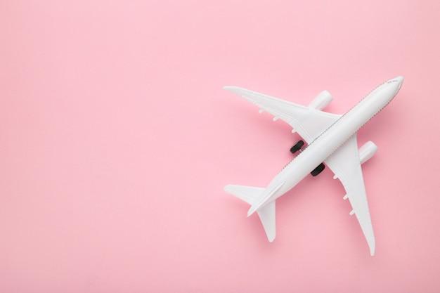 Model samolotu na różowym tle pastelowych kolorów. koncepcja podróży