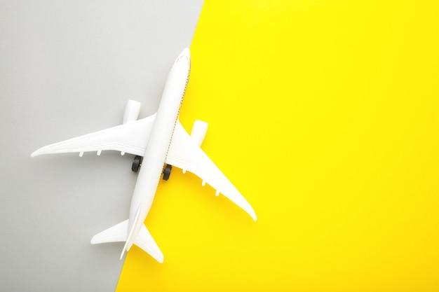Model samolotu na żółto-szarej ścianie. koncepcja podróży