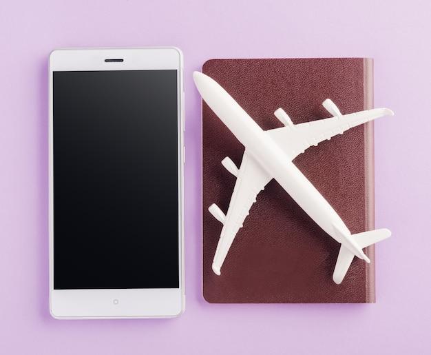 Model samolotu, samolot w paszporcie i pusty ekran smartfona