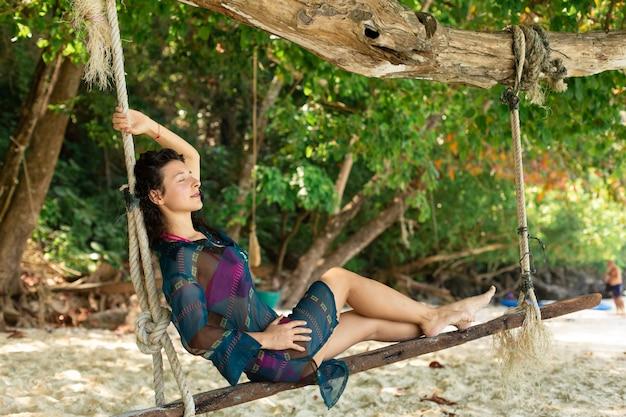 Model seksownej dziewczyny odpoczywa podczas jazdy na huśtawce przywiązanej do drzewa na tropikalnej wyspie,