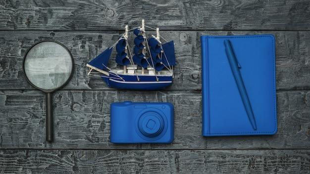 Model statku, zeszyt, lupa i kamera na drewnianym stole. pojęcie planowania podróży.