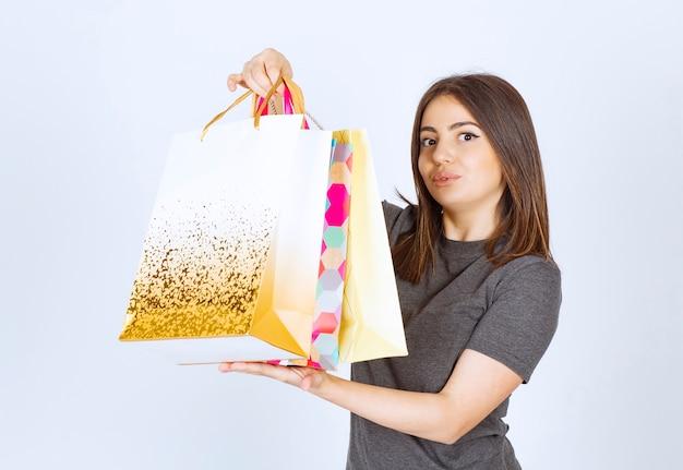 Model szczęśliwa kobieta trzyma wiele toreb na zakupy na białym tle.