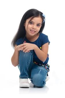 Model szczęśliwy dziecko dziewczyna pozuje do mody na białym tle