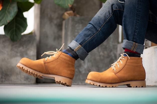 Model ubrany w niebieskie dżinsy i żółte buty na podłodze.