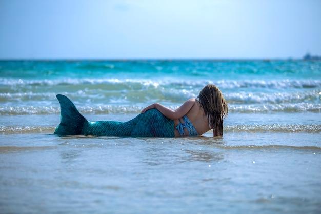 Model ubrany w strój syreny na morzu.