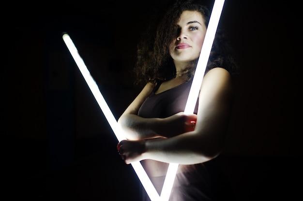 Model w kręconej brunetce plus size z dwiema długimi lampami led w czarnym pokoju.