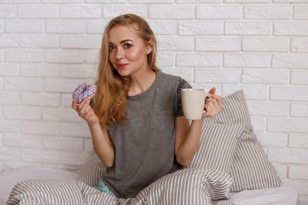 Model w łóżku rano zjada pączka i pije kawę