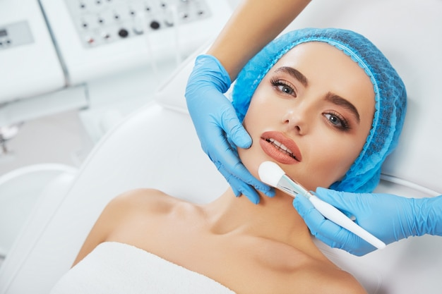 Model w niebieskiej czapce leżącej na kanapie i patrząc na kamery. ręka lekarza w niebieskiej rękawiczce dotykając jej twarzy pędzlem. głowa i ramiona, głowa i ramiona, kosmetologia