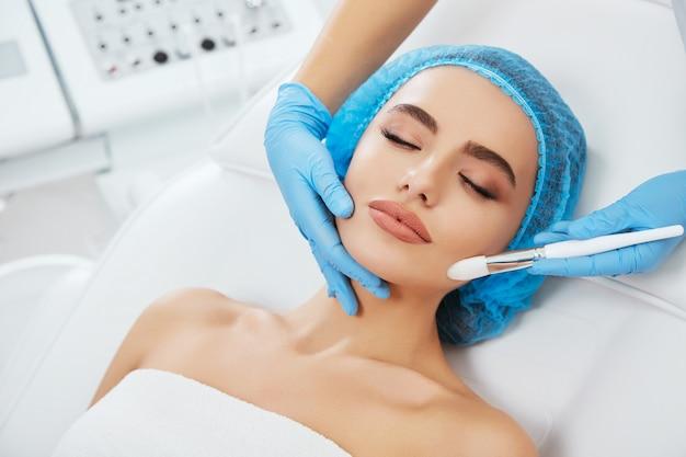 Model w niebieskiej czapce leżący na kanapie z zamkniętymi oczami. ręka lekarza w niebieskiej rękawiczce dotykając jej twarzy pędzlem. głowa i ramiona, głowa i ramiona, kosmetologia