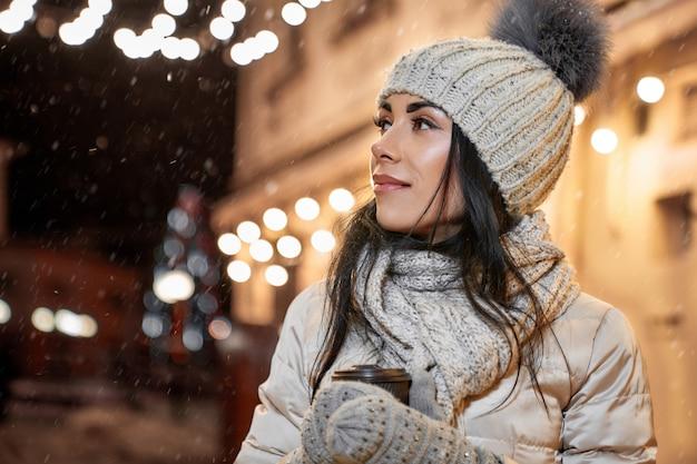 Model w odzieży zimowej ze stawianiem filiżanki kawy.