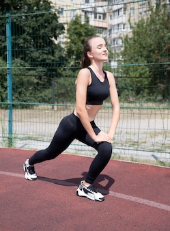 Model w sportowej na stadionie robi ćwiczenia. sport. sportsmenka