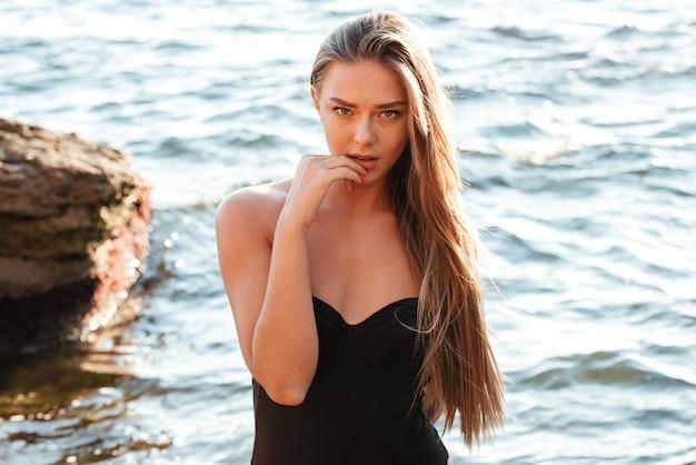 Model w stroju kąpielowym. tak sexy. patrząc z przodu. niedaleko morza