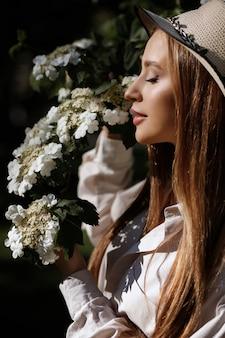 Model wącha białe kwiaty latem