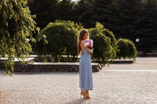 Model wieczorem na letnim spacerze. dziewczyna z bukietem kwiatów.