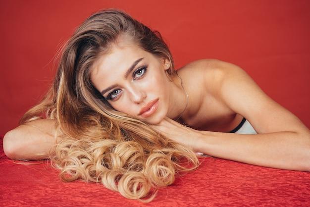 Model włosów moda kobieta blondynka z długimi włosami i naturalnym makijażem leżącym na czerwonym suknem dziewczyna pozuje