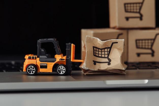 Model wózka widłowego i uszkodzony karton na laptopie z bliska. koncepcja wypadku usługi kurierskie i przesyłki