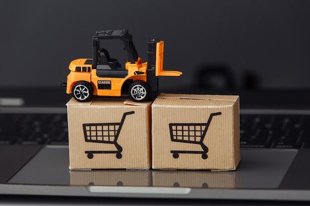Model wózka widłowego na pudełkach kartonowych na laptopie z bliska