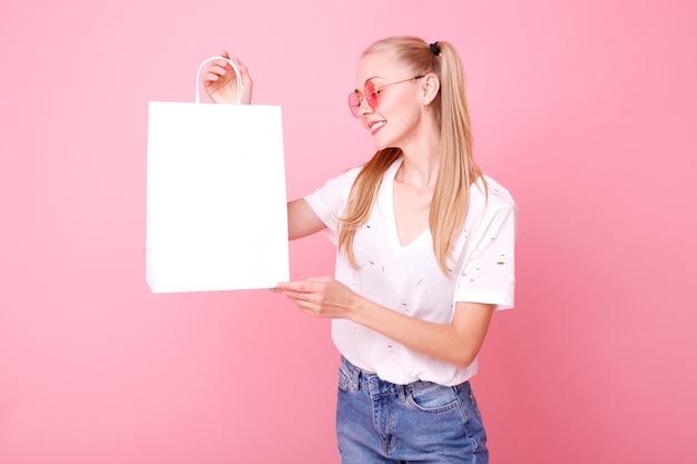 Model z białą papierową torbą w rękach w studio
