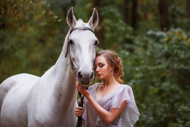 Model z białym koniem w letnim parku. letni spacer. tło jest rozmyte. efekt artystyczny, koncepcja