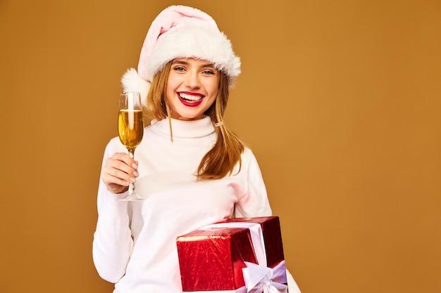 Model z czapką mikołaja i dużym pudełkiem do picia szampana na złotej ścianie