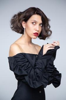 Model z modną fryzurą, czerwonymi ustami i czarną sukienką na białym tle