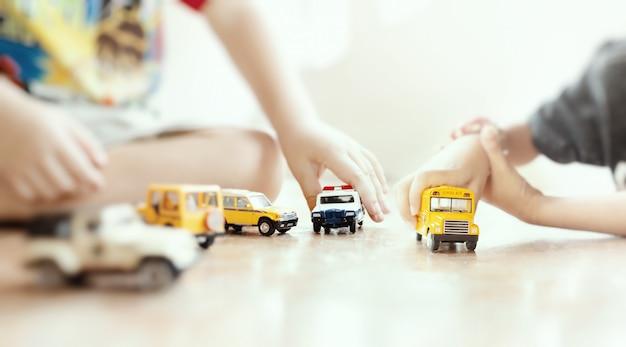 Model zabawki żółty autobus szkolny w dłoni dziecka. płytka głębia ostrości kompozycji.