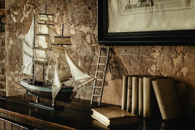 Model żaglowca z białymi żaglami stojącymi na półce ze starymi pokrytymi kurzem książkami.