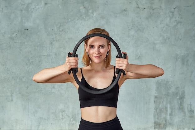 Modele fitness robi ćwiczenia ekspandera. model fitness patrzy w kamerę z ekspanderem w dłoniach opartym na szarej ścianie. szare tło, miejsce