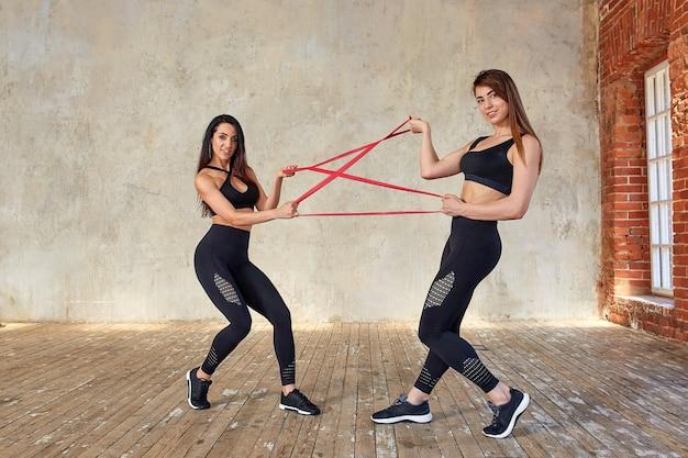 Modele fitness wykonujące ćwiczenia z gumką w studio fitness sport, uroda, zdrowie