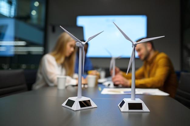 Modele wiatraków na stole. zespół młodych menedżerów, rozwijanie pomysłów w biurze it. profesjonalna praca zespołowa i planowanie, grupowa burza mózgów i praca korporacyjna, spotkanie kolegów