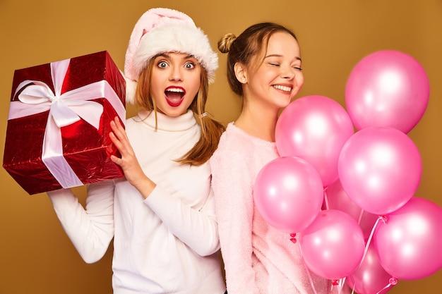 Modele z dużym pudełkiem i różowymi balonami na boże narodzenie