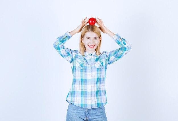 Modelka blondynka trzyma czerwone jabłko nad głową obiema rękami, uśmiechając się