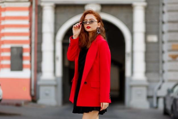Modelka demonstruje modne ubrania i akcesoria. zwyczajna czerwona kurtka, czarna krótka sukienka.