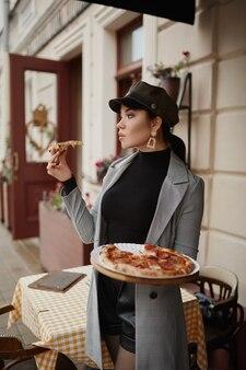 Modelka dla dorosłych dziewczyna w modnych ciuchach, trzymając smaczną pizzę i pozowanie na świeżym powietrzu w jesienny dzień