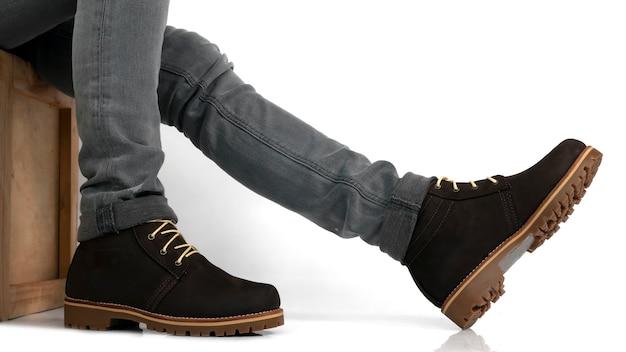 Modelka dla mężczyzn ubrana w brązowy skórzany but i jeansy siedząca na drewnianym pudełku