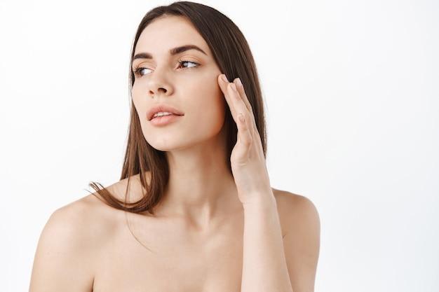 Modelka dotykając skóry pod oczami, nałóż krem przeciwzmarszczkowy przeciwzmarszczkowy, odwróć wzrok w zamyśleniu, koncepcja naturalnych kosmetyków i pielęgnacji skóry