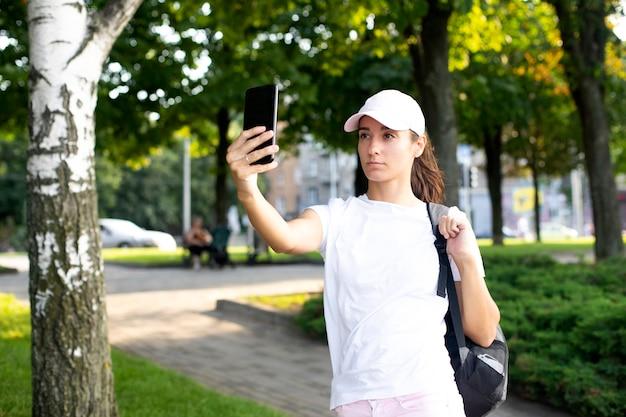 Modelka dziewczyna w białej koszulce i czapce komunikuje się przez telefon. rozmowy wideo.