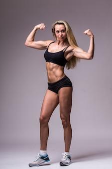 Modelka fitness w odzieży sportowej na szarym tle