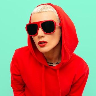 Modelka hipsterka w czerwonej bluzie z kapturem i okularami przeciwsłonecznymi w miejskim stylu