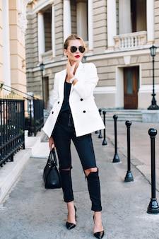 Modelka idzie ulicą na piętach. nosi okulary przeciwsłoneczne i podarte czarne dżinsy.