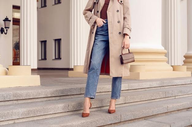 Modelka kobieta w beżowym płaszczu i dżinsach z brązową małą mini torbą pozuje na schodach