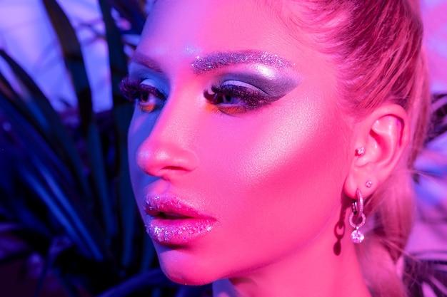 Modelka kobieta z jasnym makijażem w kolorowych jasnych neonowych światłach uv pozowanie w studio.