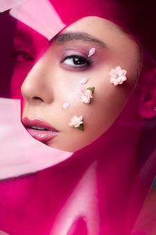 Modelka ma na sobie różowy błyszczyk i białe kwiaty