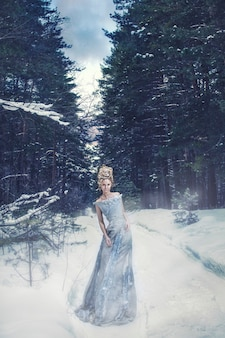 Modelka na obrazie królowej śniegu z odpowiednią fryzurą i makijażem w zimowym lesie
