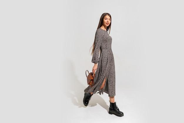 Modelka o pięknej twarzy i idealnym ciele. ubrana w modną sukienkę, trzymając w ręku brązową skórzaną torbę. pełna długość.