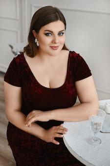 Modelka plus-size z jasnym makijażem i aksamitną sukienką siedząca przy stole we wnętrzu.