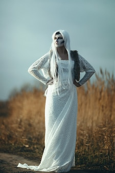 Modelka pozuje na lodowatym jeziorze z kreatywnym makijażem